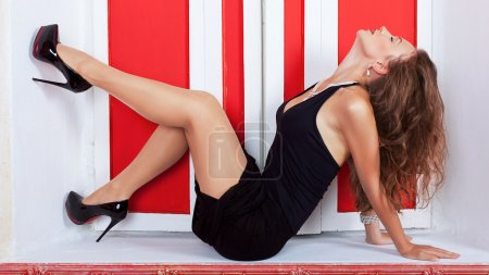 Sexy woman in evening dress on a sill in front of a red window f