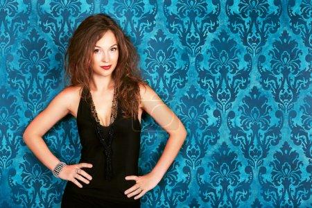 Brunette model posing against blue vintage wall smiling fashion