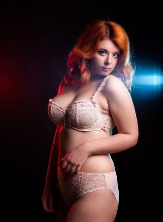 Chubby woman in underwear on black background