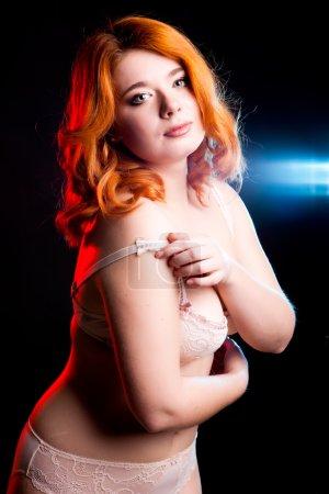 Overweight girl in underwear on black background