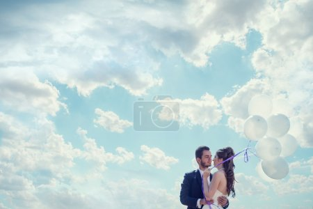 Just married bride and groom with baloons in hand over cloudy sk