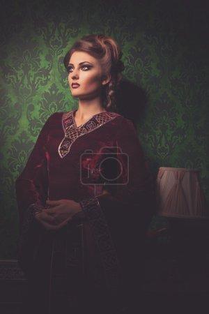 Photo pour Femme à l'intérieur vintage. Soin vintage. Intérieur rococo riche avec motif vert - image libre de droit