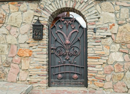forged metal gate in a stone fence