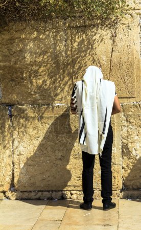 Unidentified jewish worshiper in  tallith and tefillin praying at the Wailing Wall an important jewish religious site