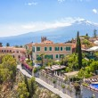 View of Taormina with Etna volcano in the back in ...