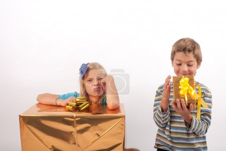 Photo for Optimist brother and pessimist sister - the brother is happy with a smaller gift box than his sister with a big one so she is very upset - Royalty Free Image
