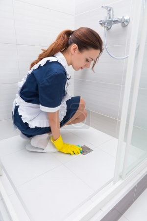 Kneeling maid cleaning shower stall