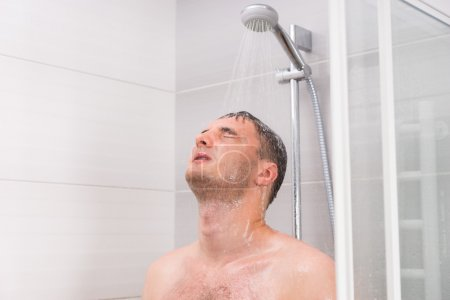 Photo for Young man with closed eyes taking a shower, standing under flowing water in shower cabin with transparent glass doors in the bathroom - Royalty Free Image