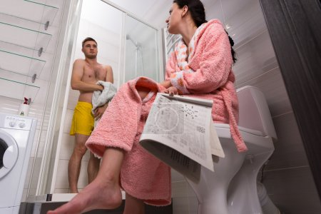 Bottom view of female in bathrobe with newspaper sitting on a to