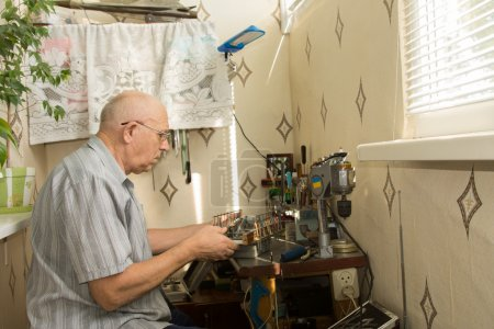 Retired man working at home on his handicrafts