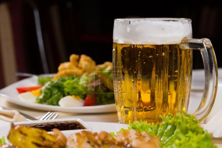 Photo for Pint of delicious cold beer with a good frothy head in a glass mug or tankard on a dinner table with food - Royalty Free Image