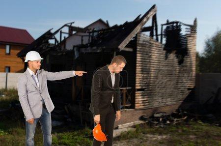 Photo pour Architecte ou ingénieur châtier un collègue et le bannir du site d'une cabane en rondins urbaine incendiée d'un geste faisant autorité et pointant du doigt - image libre de droit
