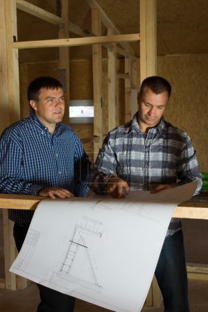 Two builders checking a blueprint together