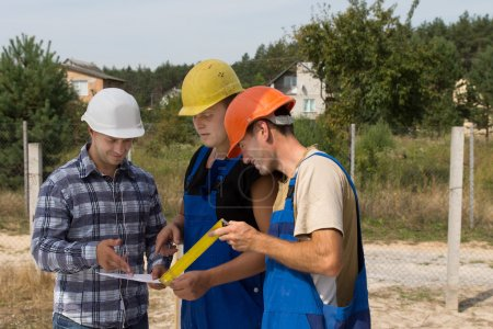 Three builders discussing paperwork on a site