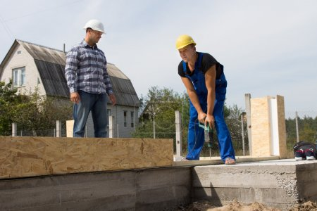 Engineer Looking at Construction Worker Drilling