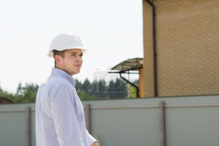 Photo pour Young Male Civil Engineer Wearing White Helmet Visits Site to See Construction Progress - image libre de droit