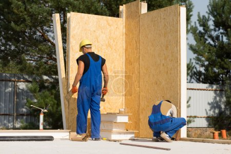 Male Construction Workers Building a House