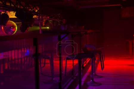 Photo for Modern bar interior decor and colorful red and purple strobe lighting illuminating a row of stylish bar stools at a counter - Royalty Free Image