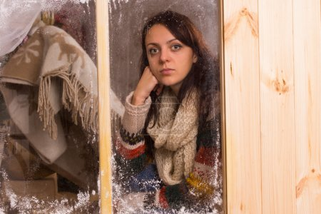 Sad young woman in a winter cabin