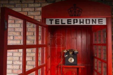 Photo for Close Up Detail of Red Public Telephone Booth with Old Fashioned Telephone Inside and Open Door - Royalty Free Image