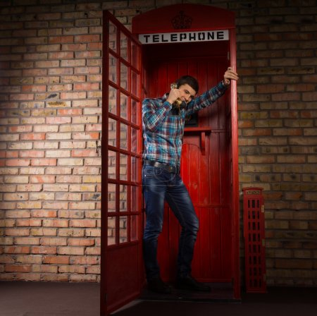 Photo for Man standing chatting in a replica red British phone booth standing leaning against the open door, full length view - Royalty Free Image