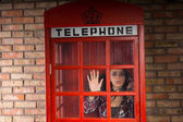 Woman peering out of a phone booth in horror