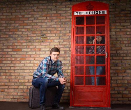 Photo pour Jeune homme ennuyé attendant que sa femme ou sa petite amie finisse de bavarder au téléphone dans une cabine téléphonique britannique rouge assise patiemment dehors sur sa valise - image libre de droit