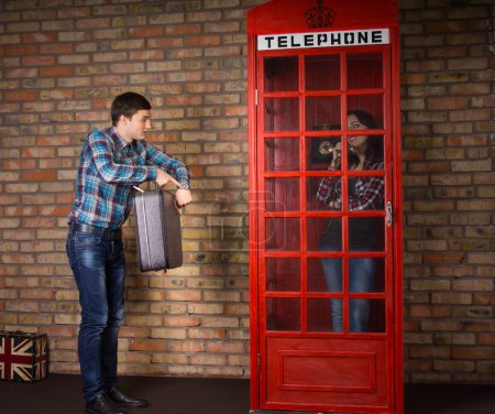 Photo pour Impatient man pointing to his watch as he stands alongside a red British telephone booth with his suitcase while his wife chats to friends on the phone - image libre de droit