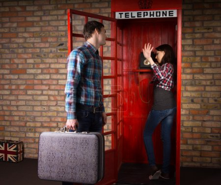 Photo pour Woman refusing to listen to her husband as he implores her to get off the phone in a public telephone booth as he has a trip to make with his suitcase - image libre de droit
