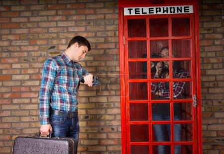 Photo pour Homme regardant sa montre-bracelet pour vérifier l'heure alors qu'il tient une valise à côté d'une cabine téléphonique rouge avec sa petite amie à l'intérieur bavarder au téléphone - image libre de droit