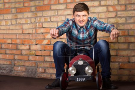Photo for Close up Young Handsome Man in Casual Outfit Riding on Vintage Toy Car on a Brick Wall Background. Emphasizing Racing Concept. - Royalty Free Image