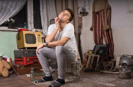 Sitting Man Scratching his Neck at Junk Room