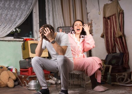 Couple in a squalid room having an argument