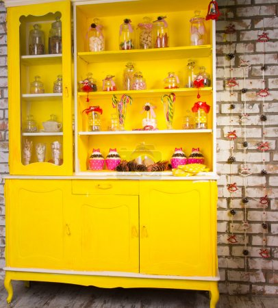 Photo for Colorful bright yellow welsh dresser with its shelves filled with decorative glass jars of kitchen ingredients and decorated with striped candy canes and ribbon - Royalty Free Image