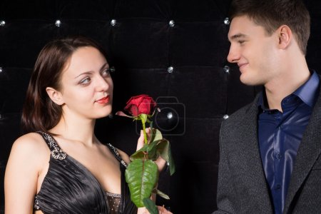 Photo for Loving couple smiling at each other with tender expressions over a single red rose symbolising Valentines Day, a proposal for her hand in marriage or and anniversary - Royalty Free Image