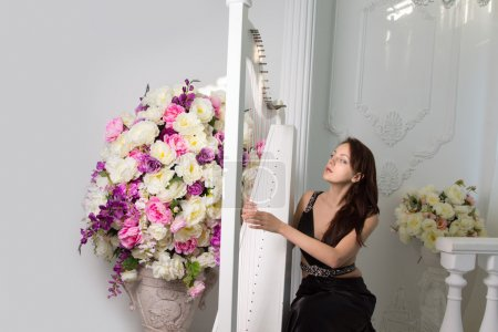 Photo pour Attractive young female classical musician playing the harp at a concert or recital sitting plucking the strings in front of a large colorful flower arrangement - image libre de droit