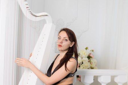 Photo pour Musicien féminin assez élégant dans l'usure noire de soirée s'asseyant jouant la harpe courant ses doigts au-dessus des cordes pendant qu'elle regarde l'appareil-photo - image libre de droit