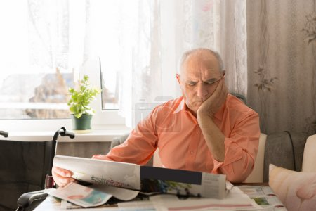 Old Man Reading Newspaper with Hand on Face
