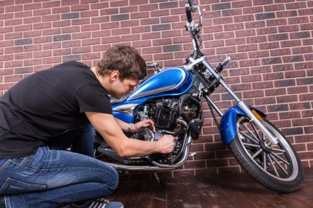 Sitting Young Guy Repairing his Motorcycle
