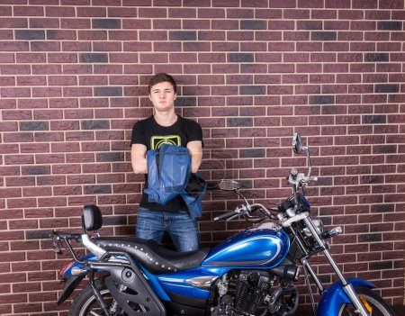 Young Man Holding his Jacket Behind his Motorcycle