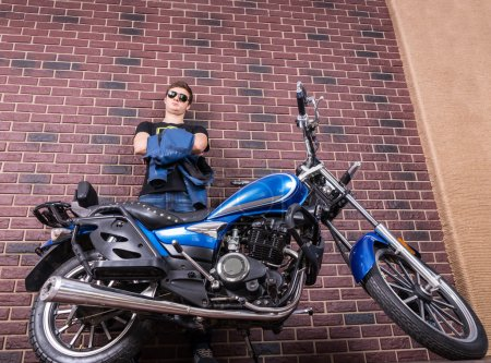 Man with Motorcycle Leaning Against Brick Wall