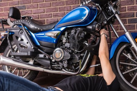 Lying Young Guy Fixing his Sports Motorbike