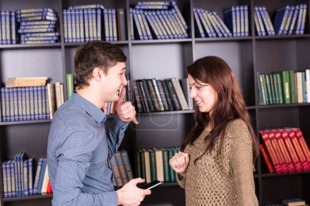 Young Couple with Mobile Phone Talking at Library