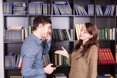 Happy Young Lovers Discussing Inside the Library