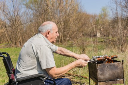Old Man on Wheelchair Grilling Sausage Outsides