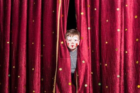 Photo pour Petit garçon mignon utilisant la peinture rouge colorée de visage et un costume regardant dehors d'entre les rideaux sur l'étape pendant qu'il attend une pantomime pour commencer - image libre de droit