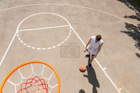 Man Dribbling Basketball in Key of Court