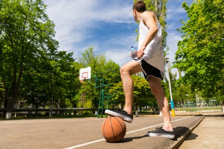 Man with Foot on Basketball Looking Towards Basket