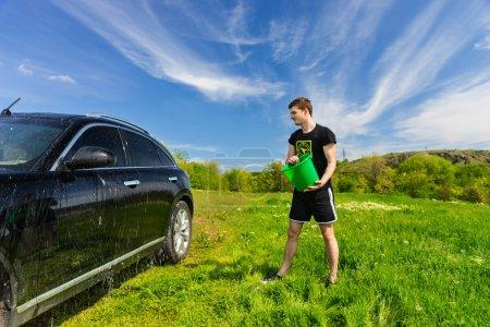 Man Washing Black Car in Green Field