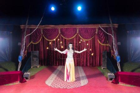Photo pour Pleine longueur de danseur de feu aux cheveux foncés exotiques portant un costume lumineux et Un appareil de baton flamboyant sur scène lit par Bright Spotlights - image libre de droit